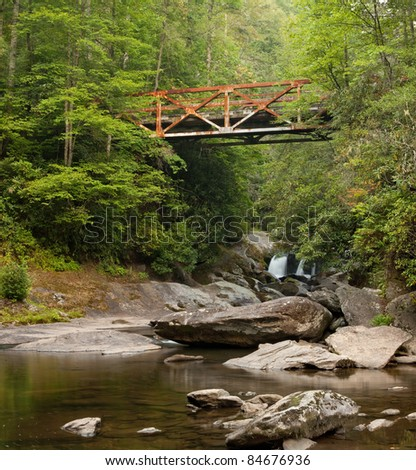 Old rusted iron bridge in the Appalachian Mountains.  This bridge crosses the Chattooga near Highlands, North Carolina - stock photo