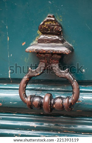Old rusted knocker on green wooden door in Paris, France - stock photo