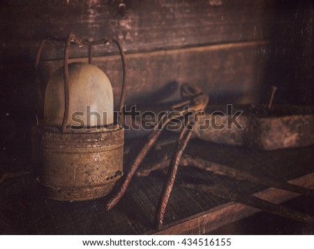 Old rusted lamp and tools in a shed in a village - stock photo