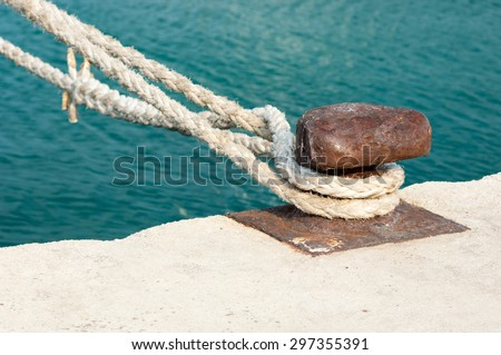 Old rusted mooring bollard with naval ropes on concrete pier. - stock photo