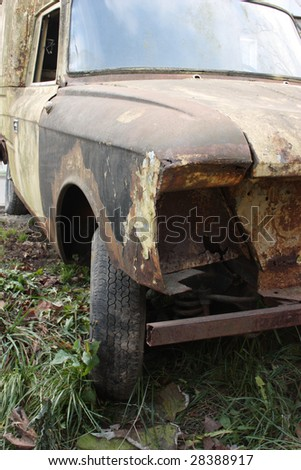 Old rusted torched car at autumn street - stock photo