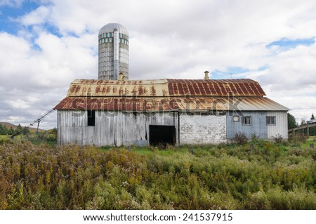 old rustic barn with silo in Quebec Country in autumn, Canada - stock photo