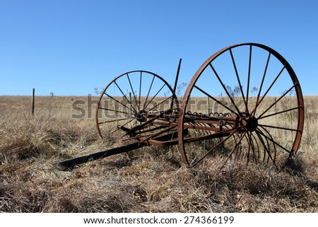 Old rustic farm equipment lies abandoned in a field. - stock photo