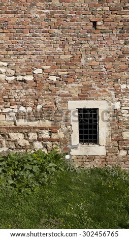 Old rustic fortress brick wall with small window with copy space. - stock photo