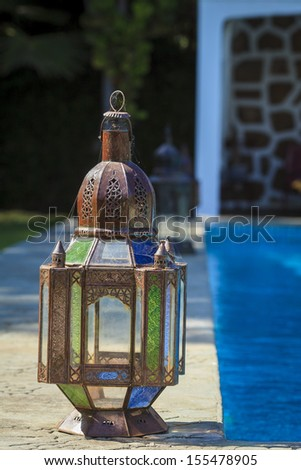 Old rustic lamp wrapped in a spider web, next to the swimming pool - stock photo