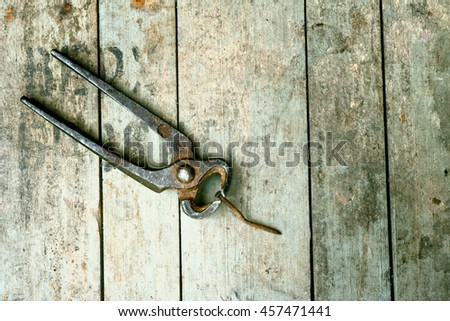 Old rustic pliers and rusty nail on the wooden background with space for text. Vintage look. - stock photo