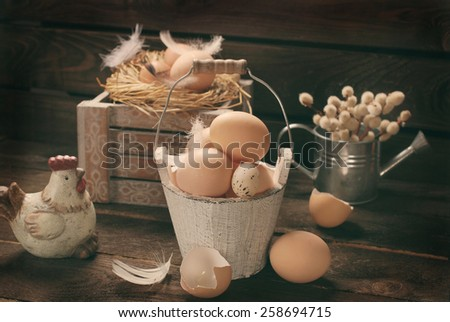 old rustic still life with eggs in vintage wooden bucket  and in nest for easter - stock photo
