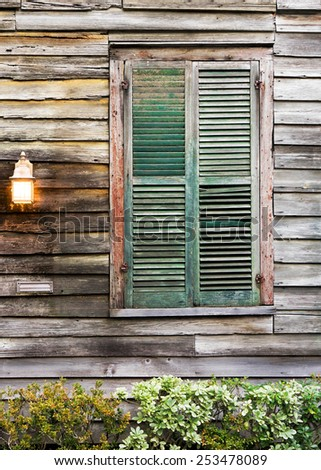 Old rustic vintage dilapidated antique house home building structure with green window shutters closed and porch light lantern glowing turned on - stock photo