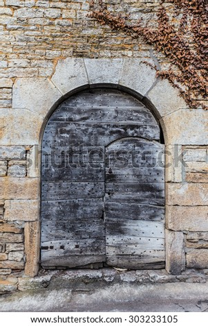 Old rustic wooden door in a stone structure