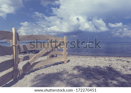 Old rustic wooden fence on a beach leading down towards the calm ocean with a yacht visible in the far distance under a cloudy blue sky - stock photo
