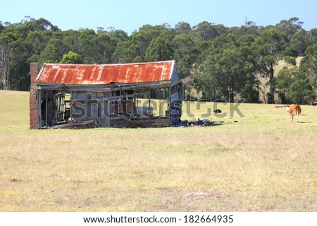 Old rusting broken down farm house on rural Australian property - stock photo