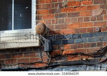 Old rusting burglar alarm bell on old building wall.