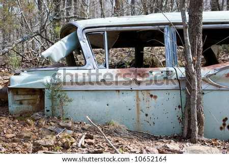 Old rusty abandoned car with bullet holes in it - stock photo