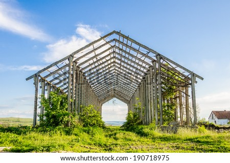 Old rusty abandoned industrial farm structure with concrete and steel beams and trusses and vegetation growing on it with a melancholic look suggesting long lasting work - stock photo