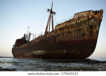 Old rusty abandoned ruined vessel, stranded in shallow water of sandy beach. - stock photo