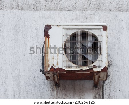 Old rusty air conditioner outdoor unit on house facade - stock photo
