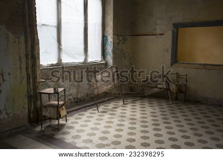 old rusty bed and cabinet in abandoned hospital in getmany, beelitz - stock photo