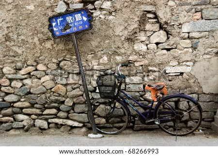 old rusty bicycle, leaning against an ancient brick wall and street sign in China - stock photo