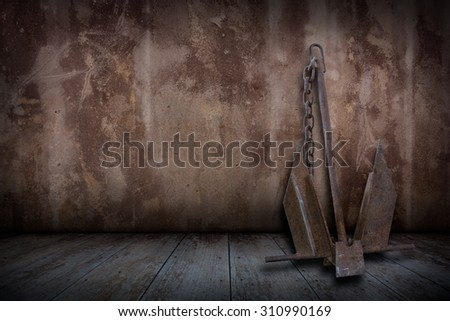 Old rusty boat anchor in plaster walls and old wooden floors, Vintage style. - stock photo