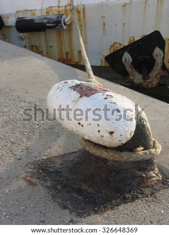 Old rusty bollard and rope on a traditional harbor pier with weathered fishing boat in the background - stock photo
