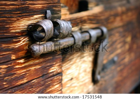 Old rusty bolt on a wooden door