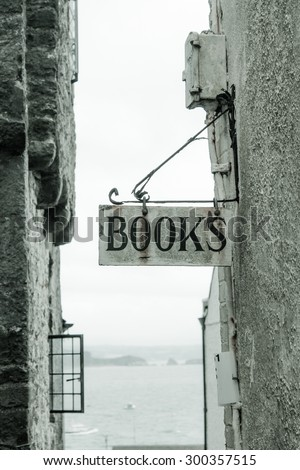 Old Rusty Book Sign on a wrought iron hanging bracket - stock photo