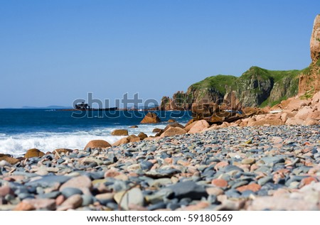 old rusty broken ship on rocks beach