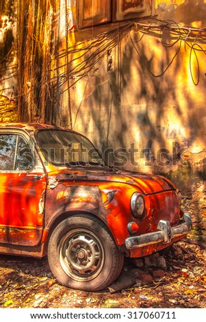 old rusty car in front of dirty wall - stock photo