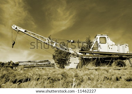 Old rusty crane in the wilderness in monochromatic sepia
