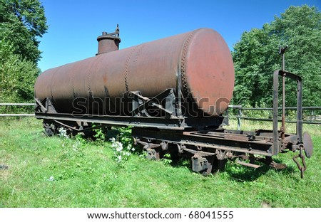 Old rusty decauville train tank on the grass - stock photo
