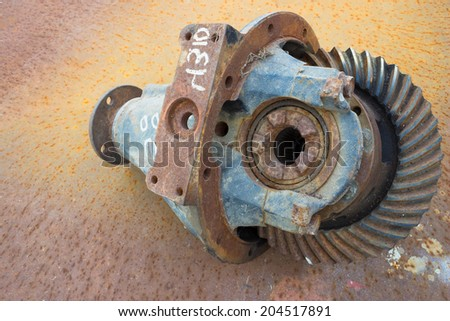 old rusty differential lying on a rusty background - stock photo