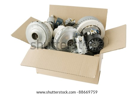 Old rusty dust motors from vacuum cleaners  are in cardboard  box at the dump. Isolated with patch - stock photo