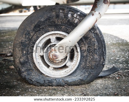 Old rusty dusty flat tire. - stock photo