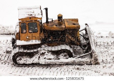 Old rusty earth digging caterpillar bulldozer machine working at building construction site - stock photo