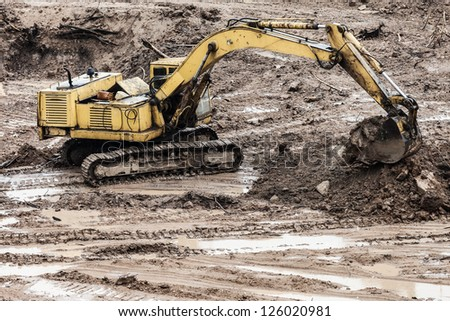 Old rusty earth digging excavator machine working at building construction site - stock photo