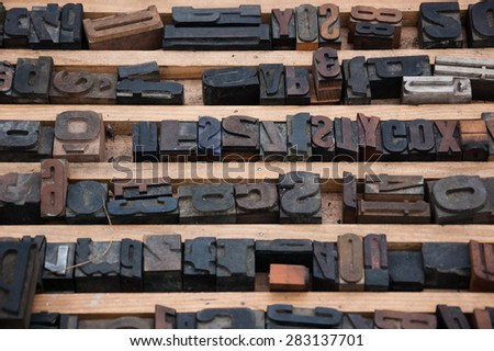 Old rusty English alphabet  letterpress and numbers printing blocks at flea market in Paris (France). Vintage background. Selective focus on the upper part of the image. - stock photo