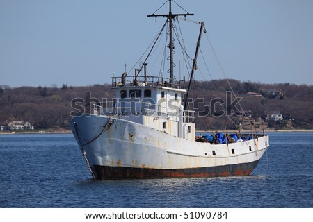 Old rusty fishing boat anchored in a protected harbor - stock photo