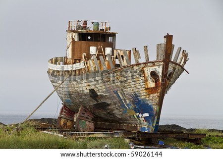 Old rusty fishing trawler being broken up on the shore, bow to camera - stock photo