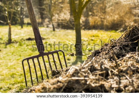 Old Rusty Garden Tools Pitchfork in the Compost Heap - stock photo