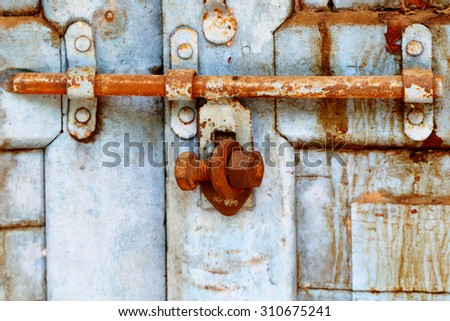 Old rusty gate Sliding lock with wood door. Locked wit nut bolt. - stock photo