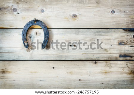 Old rusty horseshoe  hanging on a wooden background. Easy HDR effect - stock photo