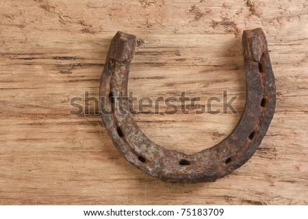 old rusty horseshoe on a wood background - stock photo