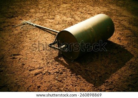 Old rusty iron barrel for maintenance of neglect tennis court. Old dry red crushed bricks surface on outdoor tennis ground. - stock photo