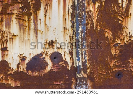 old rusty iron wall with bullet holes - stock photo