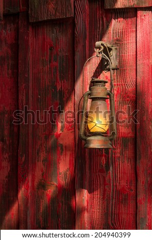 Old rusty kerosene lantern hanged on a rustic wooden wall - stock photo