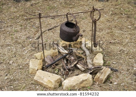 Old rusty kettle on iron frame over an unlit open fire outside in countryside - stock photo