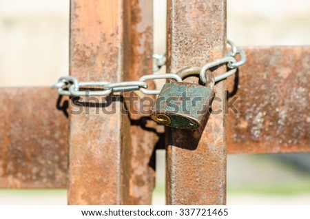 Old rusty key lock locked with a chain. rusty gate - stock photo