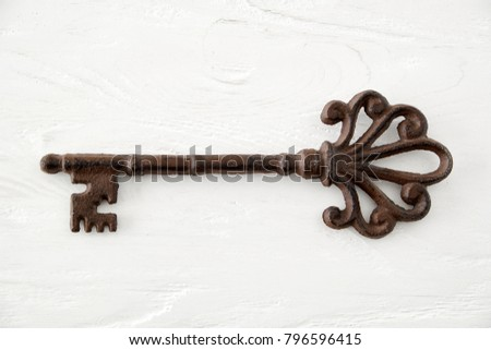 Old rusty key on aged white wooden background.