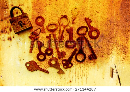 Old rusty keys and the lock on rusty with cracks grunge a background. Grunge a background with old keys - stock photo