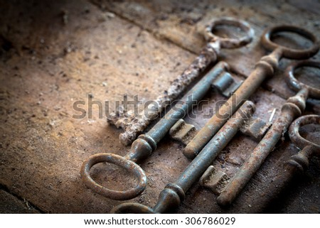 Old rusty keys on a wooden table without lock - stock photo